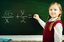 Girl Student on chalkboard writing fraction equation.
