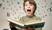 Boy with mouth wide open expression holding a book.