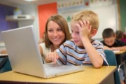 Boy on laptop with teacher.