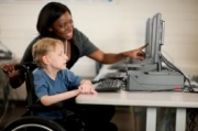 Child in wheelchair looking at computer with teacher.