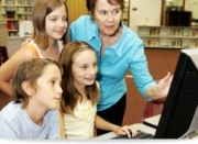 Three students with teacher looking at computer screen.